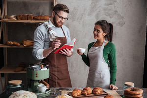 Image of cheerful loving couple bakers standing near bread and croissants drinking coffee. Looking at notebook.