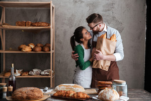 Image of cheerful loving couple bakers standing near bread and hugging. Looking aside.