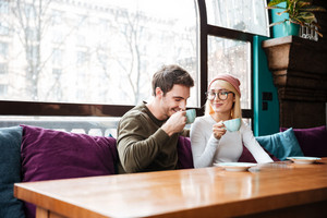 Image of cheerful loving couple sitting in cafe and drinking coffee. Look aside.