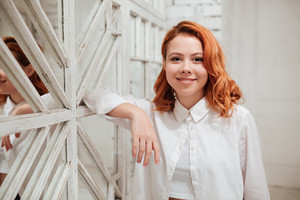Image of cheerful redhead young woman dressed in white shirt standing near mirror in cafe. Looking at camera.