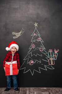 Image of cheerful screaming child wearing hat holding a big gift near Christmas tree drawing on blackboard. Looking at camera.