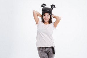 Image of cheerful woman wearing virtual reality device while holding joystick over white background. Look aside.