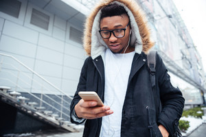 Image of cheerful young african man holding his cellphone in hands and chatting while listening music