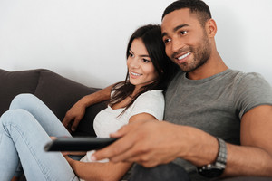 Image of cheerful young couple hugging and watching TV on sofa at home.