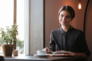 Image of cheerful young lady sitting at the table reading book in cafe and looking at camera while drinking coffee.
