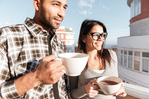 Image of cheerful young loving couple drinking coffee while standing on roof. Look aside.