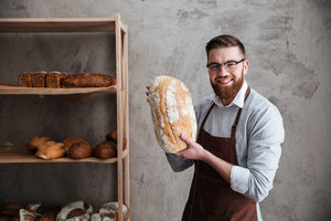 Image of cheerful young man baker standing at bakery holding bread. Looking at camera.