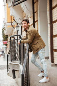Image of cheerful young man walking on the street and looking aside.