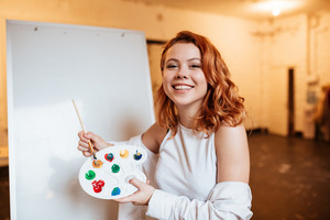 Image of cheerful young woman painter with red hair standing over blank canvas in artist workshop. Look at camera while holding palette and paintbrush.