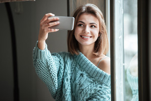 Image of cheerful young woman sitting near window in cafe and make a selfie by her phone.