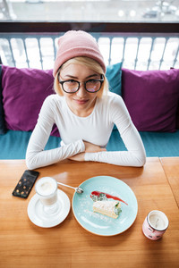 Image of cheerful young woman wearing hat and glasses eating cake and drinking coffee while sitting in cafe.