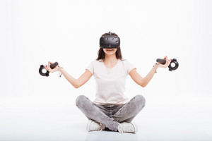 Image of cheerful young woman wearing virtual reality device holding joysticks sitting over white background.