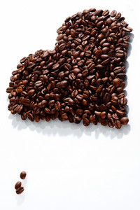 Image of coffee beans in shape of heart on white background