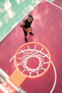 Image of concentrated african basketball player practicing for basketball. Looking at basketball hoop.