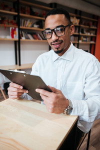 Image of concentrated african businessman wearing glasses sitting at the table holding notepad and looking at camera. Coworking.