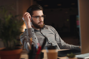 Image of concentrated bearded designer dressed in shirt working late at night and looking at computer. Touching eyeglasses.