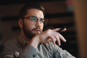 Image of concentrated bearded web designer dressed in shirt working late at night and looking at computer. Holding pen.