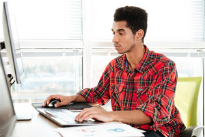 Image of concentrated handsome african student sitting in room and typing by keyboard while looking at computer.