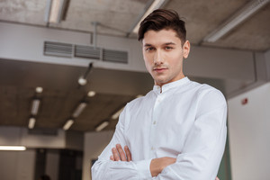Image of concentrated man dressed in white shirt standing with arms crossed indoors. Coworking. Looking at camera.