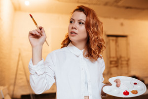 Image of concentrated redhead young woman painter with oil paints and palette painting. Look aside.
