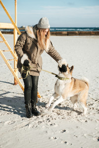 Image of concentrated young woman walks in winter beach with dog on a leash.