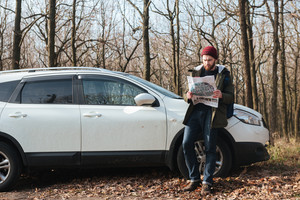 Image of confused bearded man wearing hat looking at map in the forest standing near car.