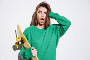Image of confused skater lady dressed in green sweater standing isolated over white background with skateboard.