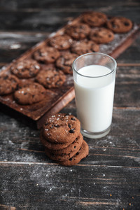 Image of cookies on desk on dark wooden table at bakery with milk