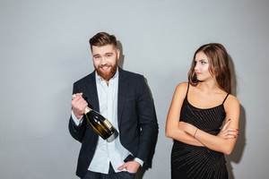 Image of couple with champagne. woman is not happy