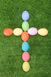 Image of cross made of easter eggs on green grass
