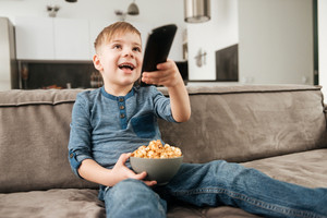 Image of cute boy sitting on sofa holding remote control while watching TV and holding popcorn in hands.