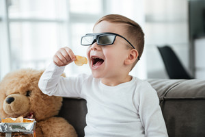 Image of cute little boy wearing 3d glasses sitting on sofa with teddy bear at home and watching TV while eating chips.