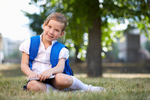 Image of cute schoolgirl with backpack sitting on grass in summer park