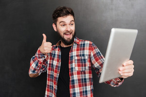 Image of excited man dressed in shirt in a cage makes thumbs up gesture while using tablet computer