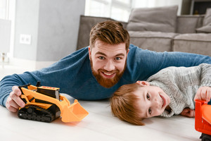 Image of father dressed in blue sweater playing toys with his little cute son indoors