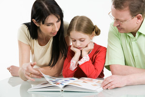Image of father, mother and their daughter looking through interesting book together