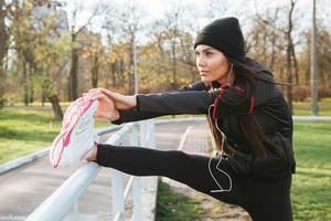 Image of fitness lady in warm clothes and headphones in autumn park make sport exercise