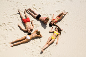 Image of five young people resting on the sand