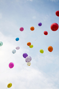 Image of flying balloons of different colors right up into blue sky