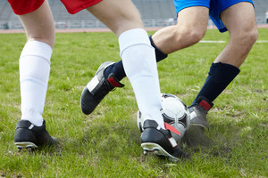 Image of footballers legs kicking soccer ball on stadium