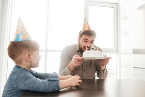Image of funny bearded young father try to eating birtday cake of his little son.