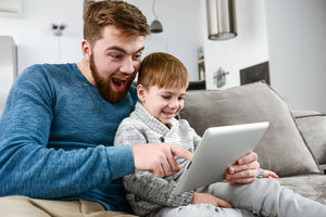 Image of funny family using tablet computer indoors. Look at tablet computer.