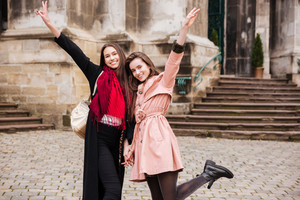 Image of funny girls in coats. on the street
