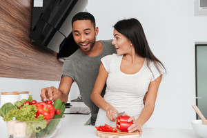 Image of funny young couple in the kitchen cooking. Man takes away the products.