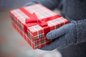 Image of gloved hand of guy holding box with Christmas present