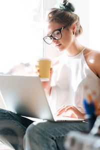 Image of gorgeous young lady wearing glasses sitting near window at the home drinking juice and using laptop computer. Look at laptop.