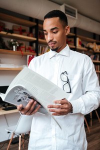Image of handsome african businessman standing in library and reading magazine. Look at magazine.