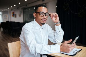 Image of handsome african businessman wearing glasses sitting at the table chatting by phone. Coworking.