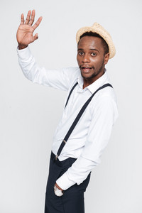 Image of handsome african man wearing hat posing in studio and waving. Isolated over white background. Look at camera.