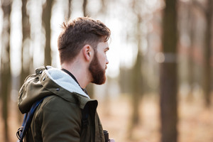 Image of handsome bearded man standing in the forest. Look aside.